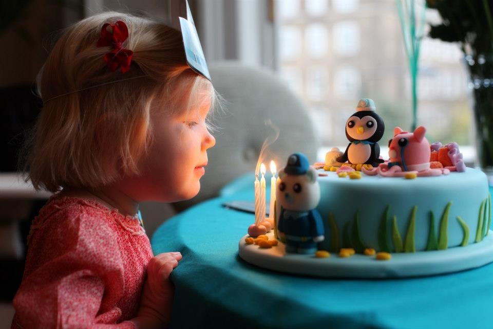 Little girl blowing candles out on Octonauts celebration cake